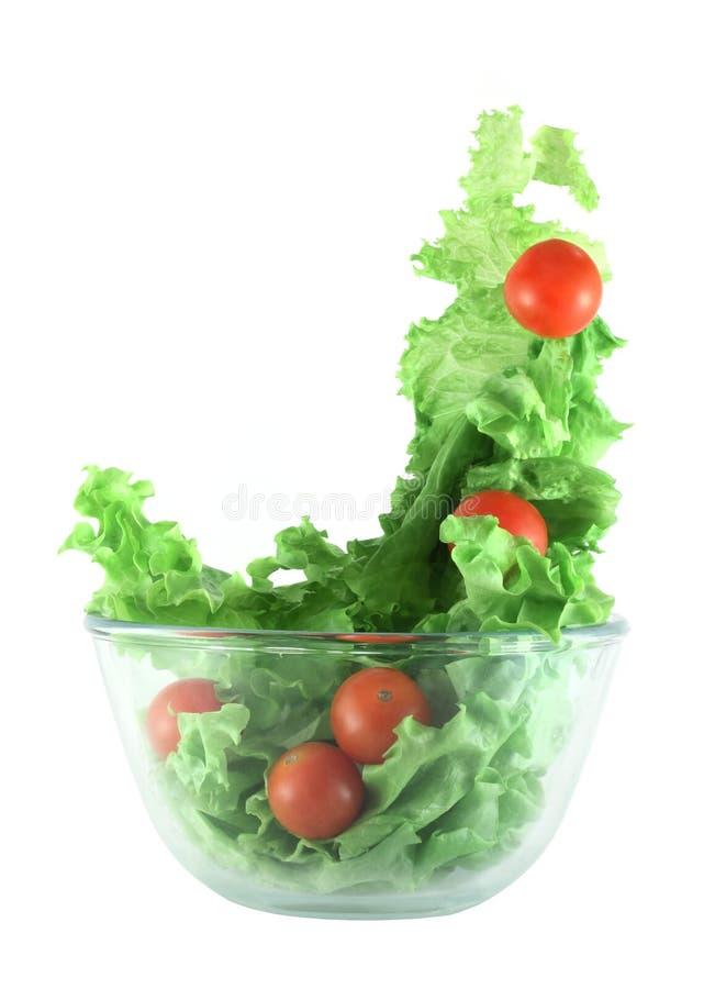 Alface clara e tomates que voam o conceito da salada fotos de stock
