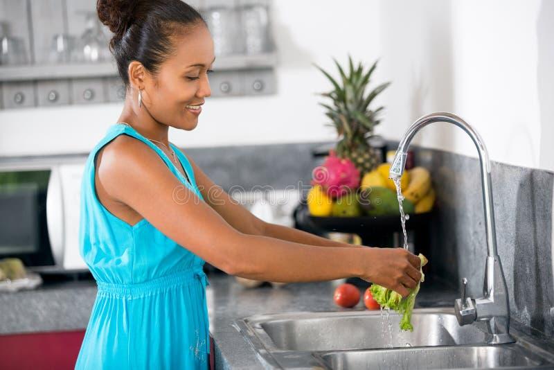 Alface de lavagem da mulher na banca da cozinha fotografia de stock royalty free