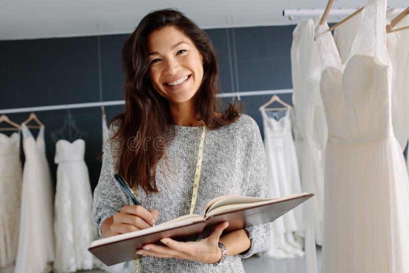 Alfaiate asiático da mulher que trabalha no boutique nupcial foto de stock royalty free