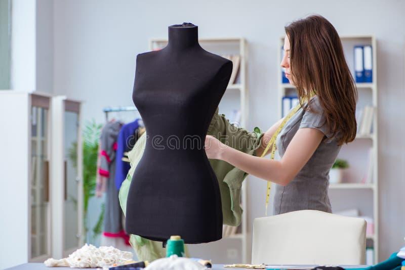 Alfaiate da mulher que trabalha em um fá de medição de costura da costura da roupa foto de stock