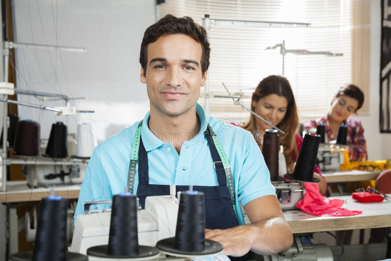 Alfaiate de sorriso Sitting At Workbench na fábrica da costura imagens de stock royalty free