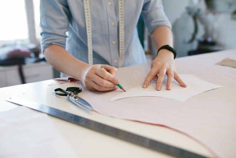 Alfaiate fêmea Making Sewing Patterns na tabela foto de stock