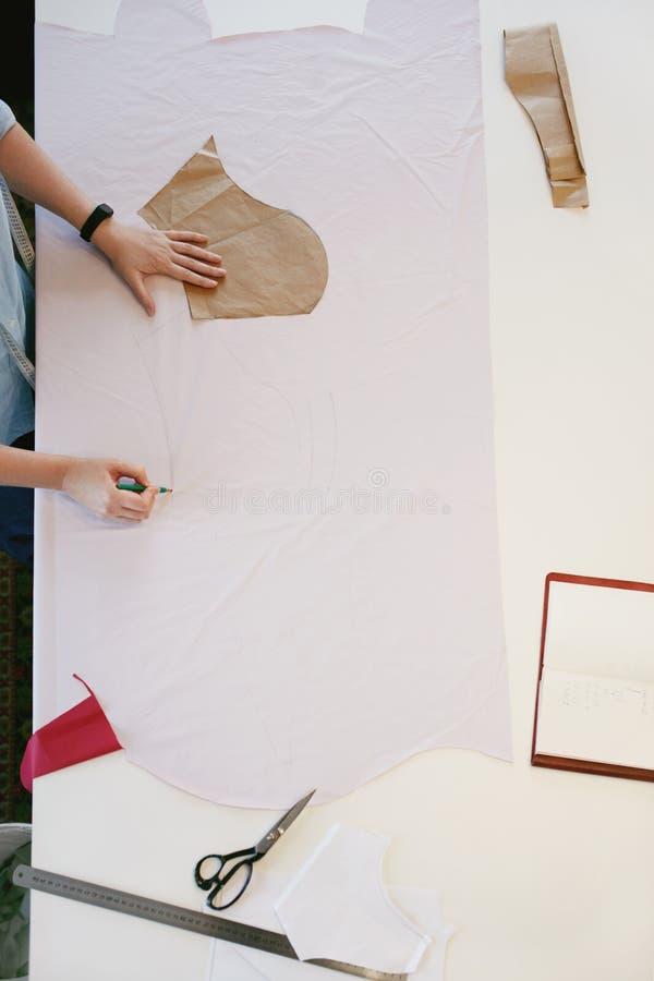 Alfaiate fêmea Making Sewing Patterns na tabela fotografia de stock