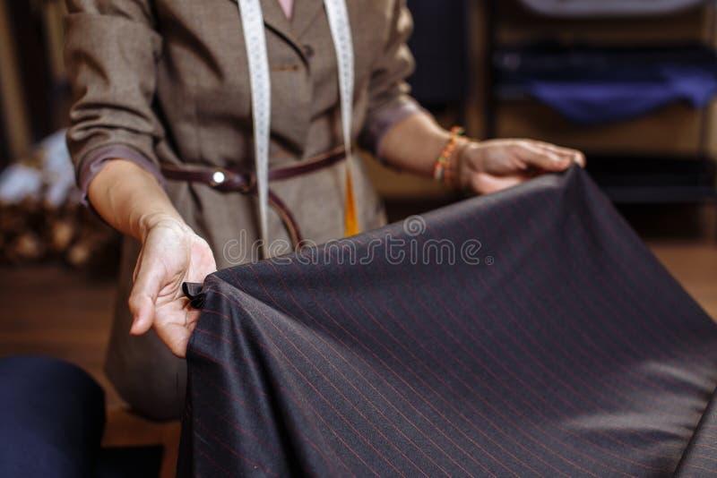 Alfaiate fêmea que escolhe a tela para o corte do teste padrão Indústria do desgaste de homens, costurando o conceito do processo fotos de stock