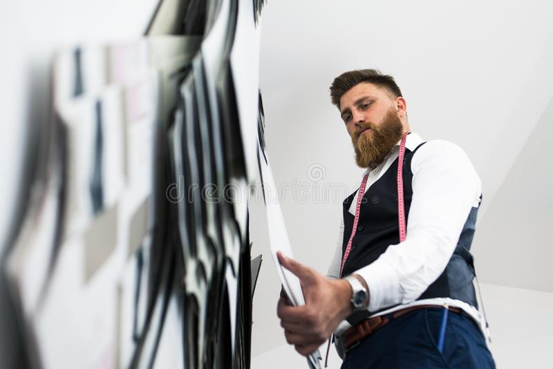 Alfaiate novo da barba que trabalha no projeto novo da roupa imagem de stock royalty free