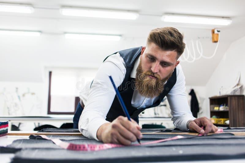 Alfaiate novo da barba que trabalha no projeto novo da roupa imagem de stock