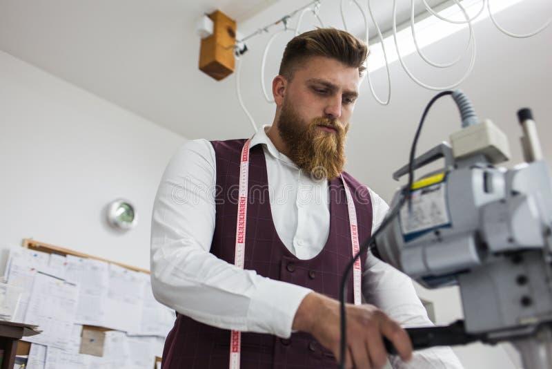 Alfaiate novo da barba que trabalha no projeto novo da roupa foto de stock