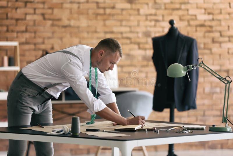 Alfaiate novo que trabalha com costurar testes padrões na oficina foto de stock