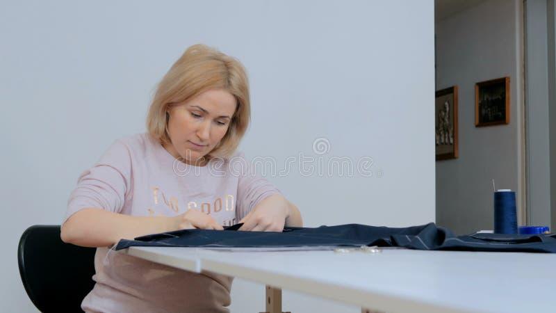 Alfaiate profissional, desenhador de moda que trabalha no estúdio da costura imagens de stock