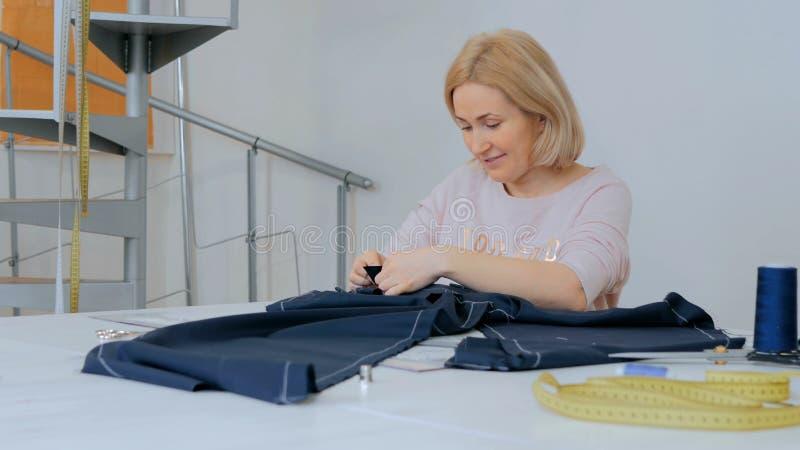 Alfaiate profissional, desenhador de moda que trabalha no estúdio da costura foto de stock