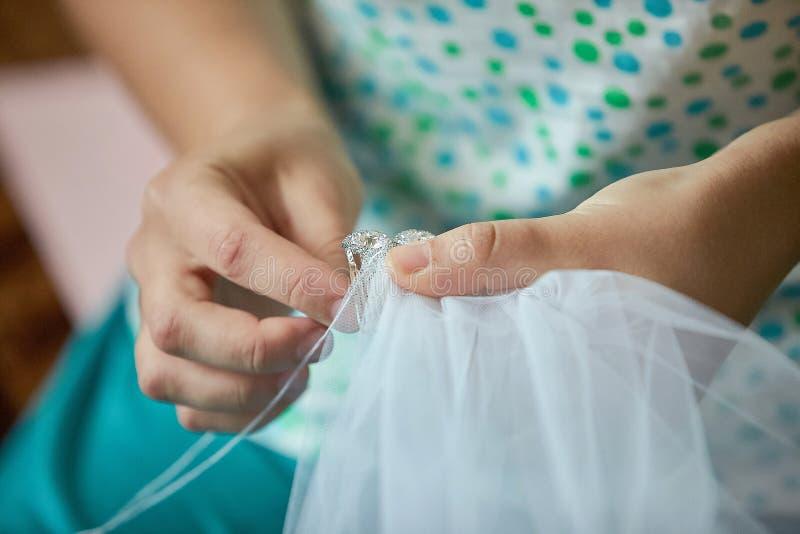 Alfaiate que costura o véu de uma noiva Feche acima das mãos imagem de stock