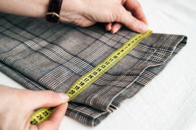 Alfaiate que usa uma medida da fita medir a largura das calças imagem de stock royalty free