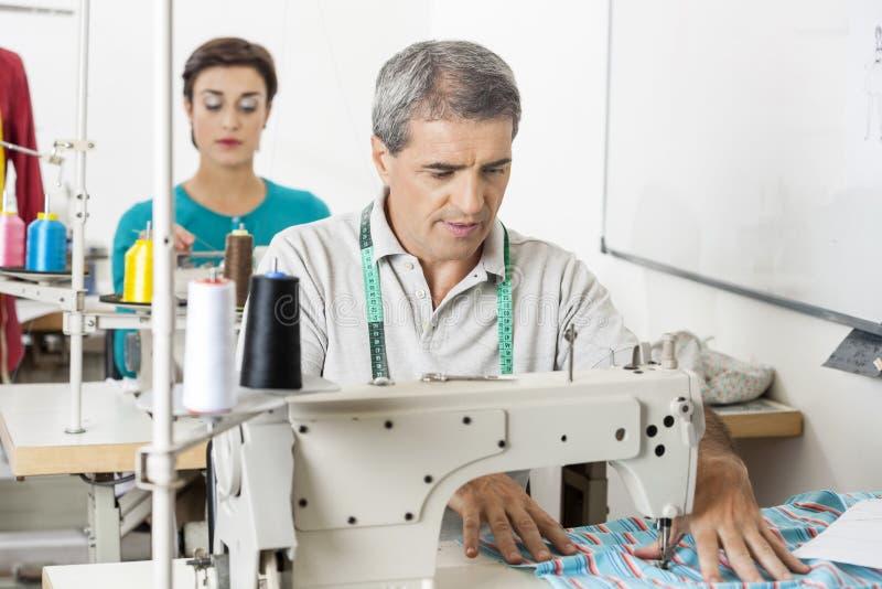 Alfaiate Using Sewing Machine na fábrica imagens de stock royalty free