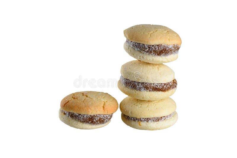 Alfajores m?rdegskakakakor som fylls med karamell och rullas i kokosn?t N?rbild isolerad bild arkivfoto