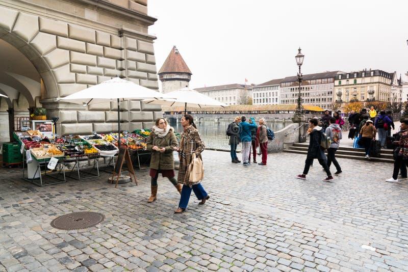 Alfalfa, LU/Suiza - 9 de noviembre de 2018: muchos peatones y transeúntes y gente ocupados que cruzan un puente y una plaza w imagen de archivo libre de regalías