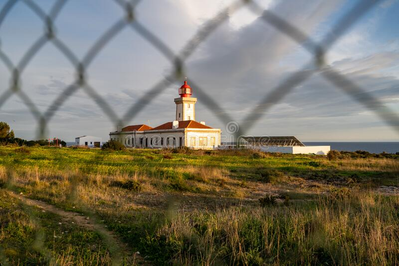 Alfanzina Lighthouse, shot through a chain link fence at dusk. The lighthouse is surrounded by fencing, near the town of Carvoeiro.  stock photo