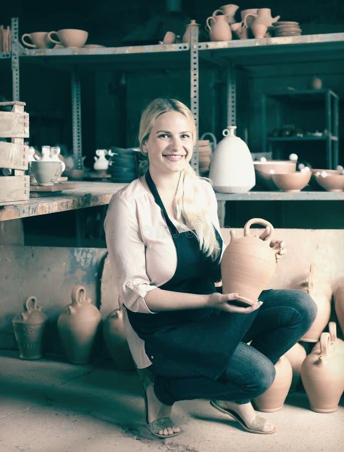 Alfarero de la mujer adulta que lleva los buques de cerámica fotos de archivo