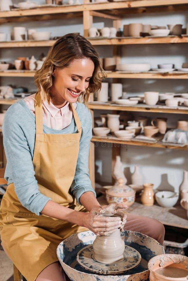alfarero de sexo femenino sonriente que hace el pote de cerámica en la rueda de la cerámica imagen de archivo libre de regalías