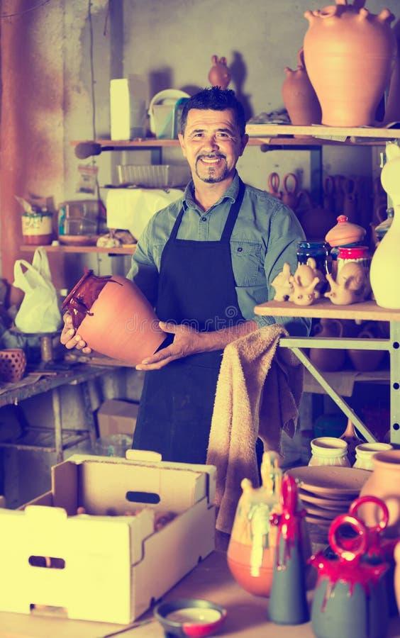 Alfarero del hombre que sostiene los buques de cerámica en taller foto de archivo