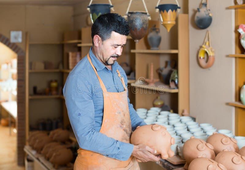 Alfarero del hombre que sostiene los buques de cerámica en taller imagen de archivo