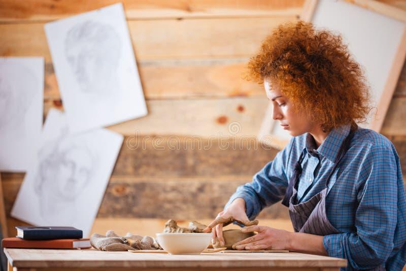 Alfarero serio de la mujer que crea platos con la arcilla por las manos foto de archivo libre de regalías