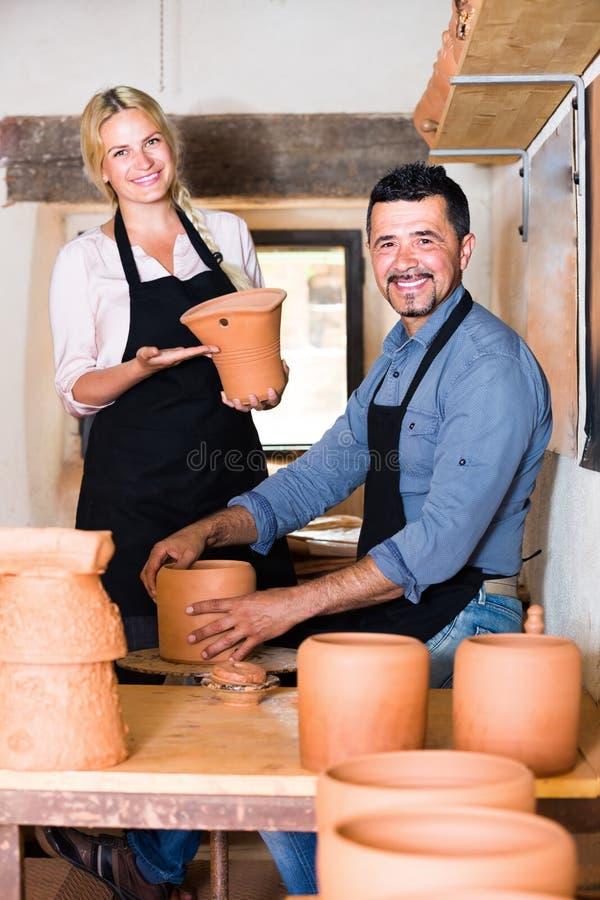 Alfarero sonriente del hombre que sostiene los buques de cerámica imagenes de archivo