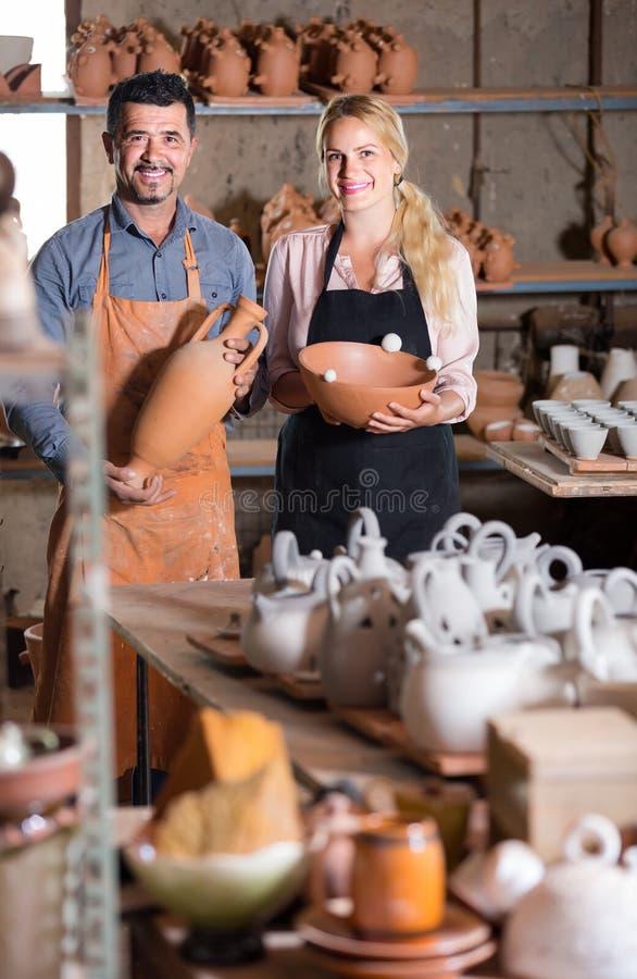 Alfareros del hombre y de la mujer que sostienen los buques de cerámica en taller fotografía de archivo