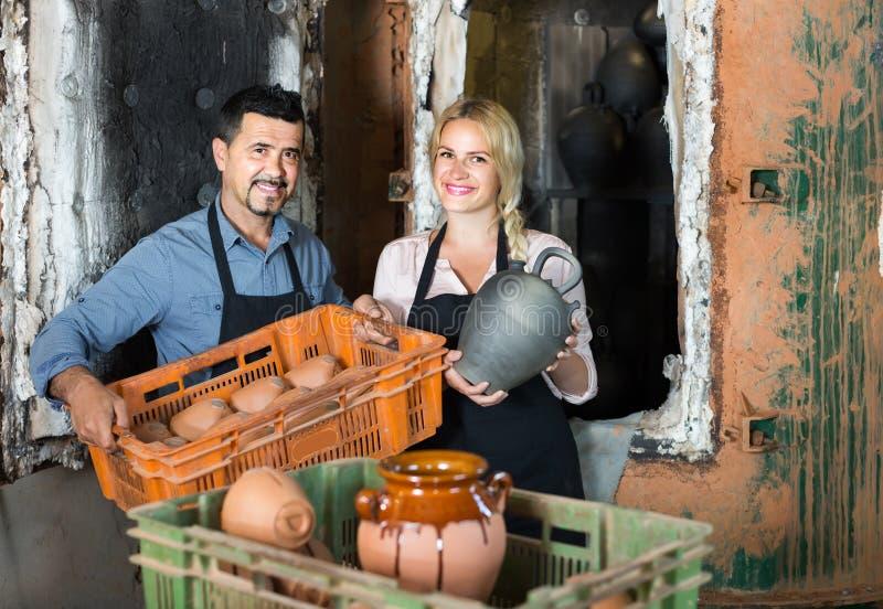 Alfareros del hombre y de la mujer que sostienen los buques de cerámica en taller imagenes de archivo