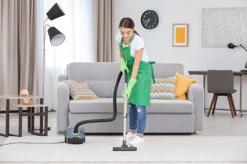 Alfombra de la limpieza de la mujer con vacío en sala de estar imagen de archivo libre de regalías