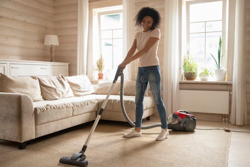 Alfombra de limpieza del vacío de la mujer de la raza mixta en sala de estar imagenes de archivo