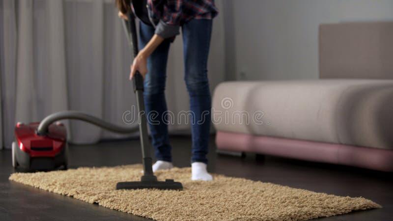 Alfombra hoovering femenina del sitio durante la limpieza general, funcionamiento de la casa, orden imagenes de archivo