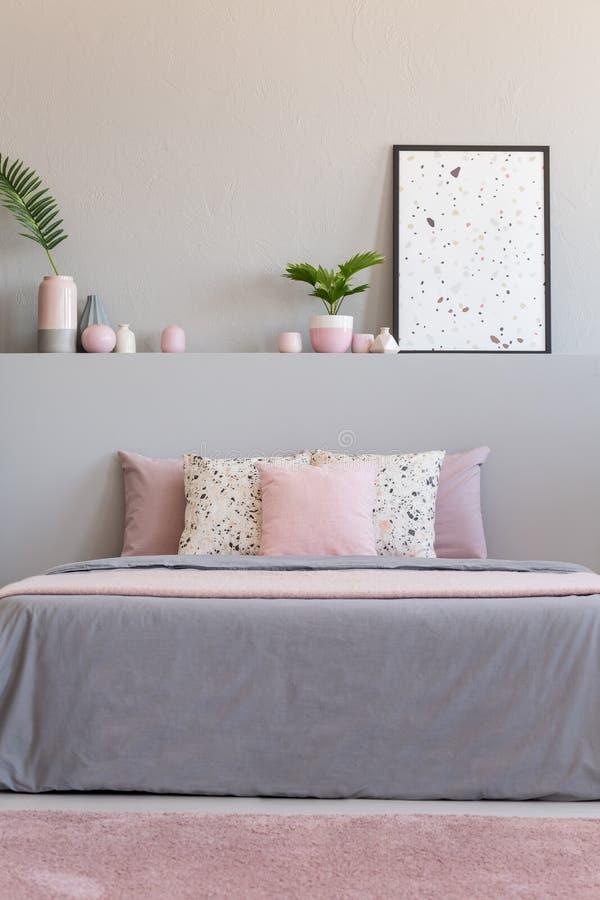 Alfombra rosada delante de la cama gris con los amortiguadores en interior del dormitorio con las plantas y el cartel Foto verdad foto de archivo