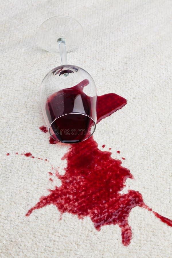 Alfombra sucia del vidrio de vino rojo. imagen de archivo