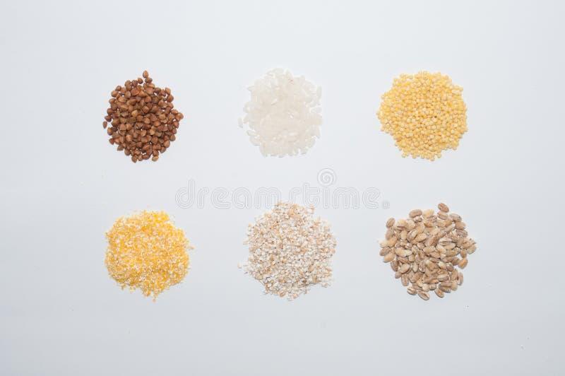 Alforfón, arroz, mijo, maíz y cebada de las gachas de avena en el fondo blanco Dieta y consumición sana imagenes de archivo