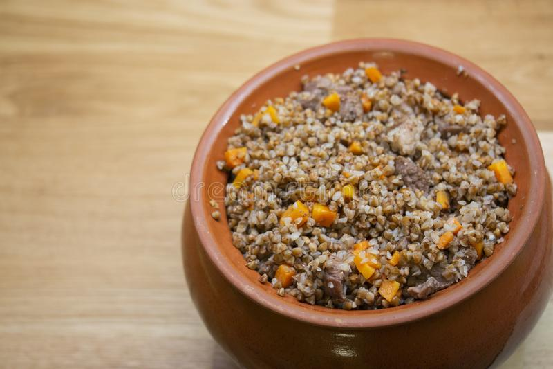 Alforfón con las zanahorias y la carne cocidas en un pote de arcilla en una tabla de madera foto de archivo