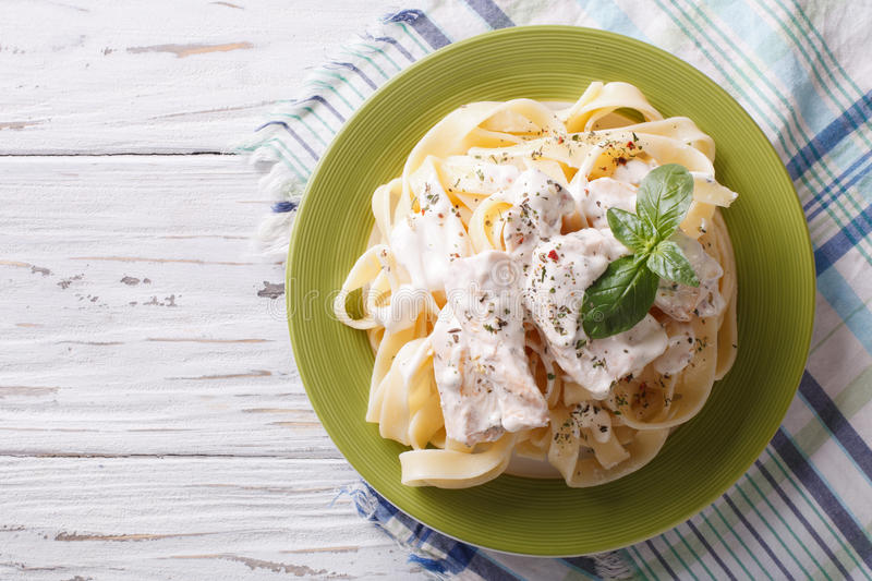 Alfredo pasta in cream sauce with chicken. horizontal top view. Alfredo pasta in cream sauce with chicken on a plate. horizontal view from above royalty free stock images