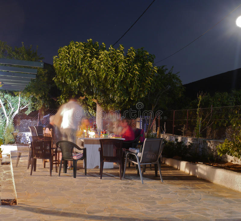 Alfresco dinner on a patio in Greece. Blurred images of people, a table and chairs royalty free stock images