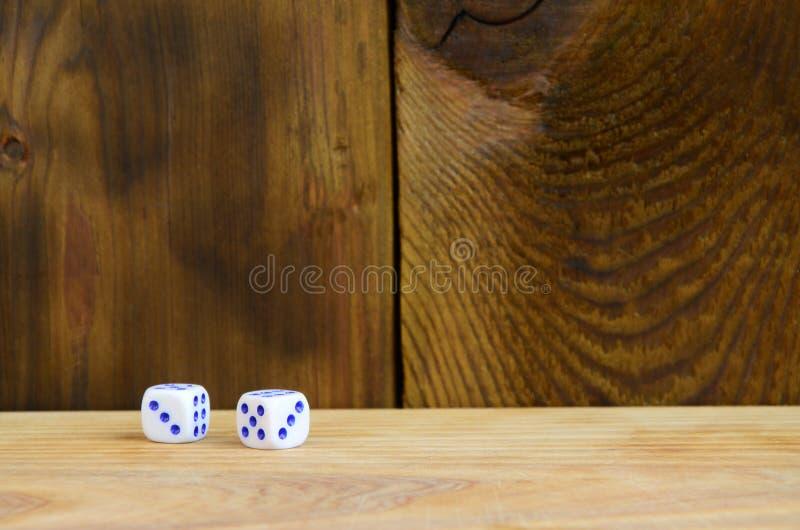 Algún dado miente en la superficie de la madera natural Los artículos para generar numeran a partir del uno a seis bajo la forma  imagen de archivo