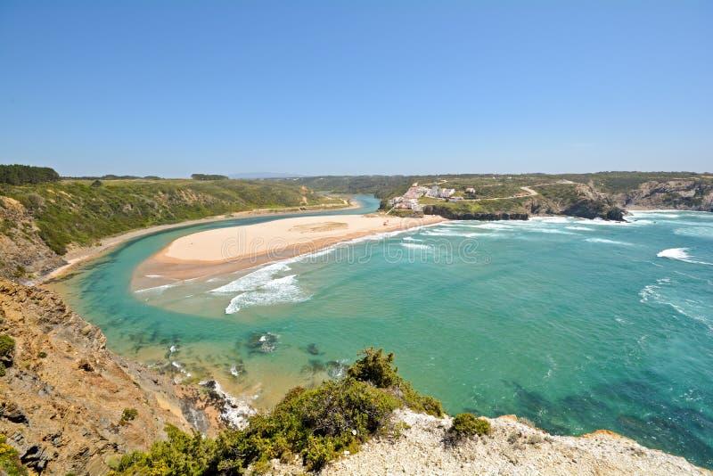Algarve: Opinión panorámica a Praia de Odeceixe, playa de la persona que practica surf y poco pueblo cerca de Aljezur, Portugal fotografía de archivo libre de regalías