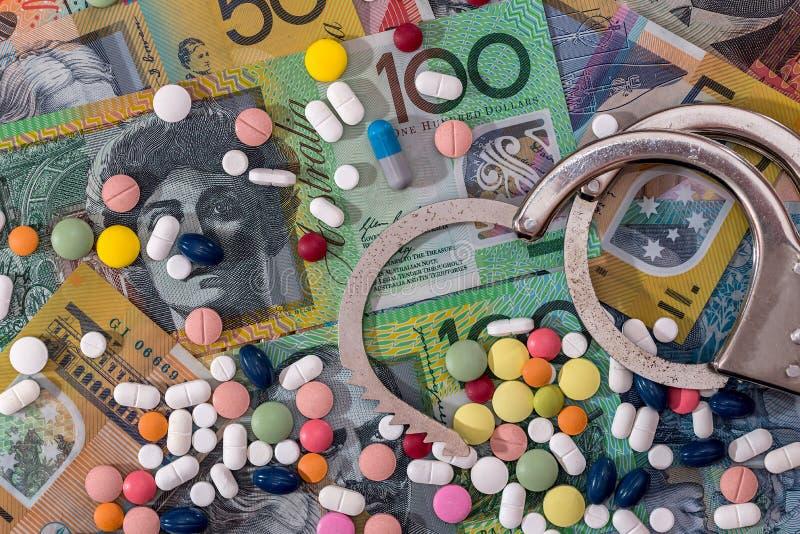 Algemas abertas com os comprimidos dispersados no fundo do dólar australiano fotos de stock royalty free