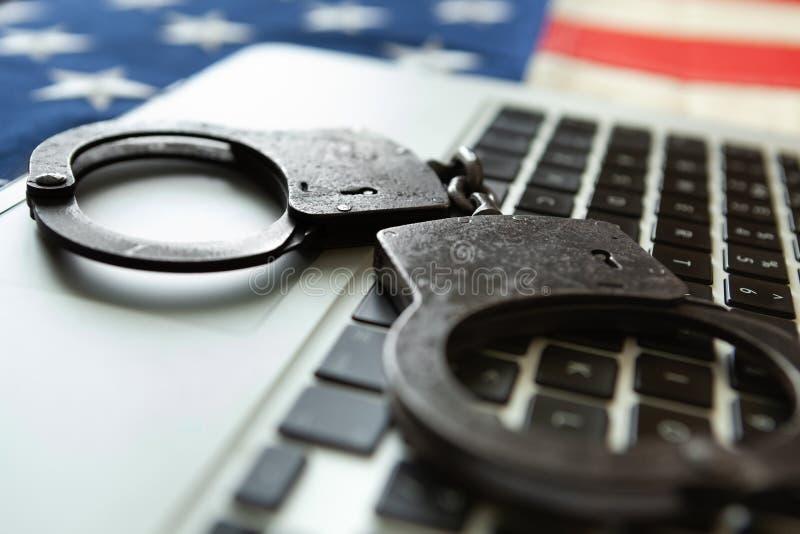 Algemas do metal sobre um portátil com uma bandeira velha dos EUA no fundo - fim acima do tiro do estúdio imagem de stock royalty free
