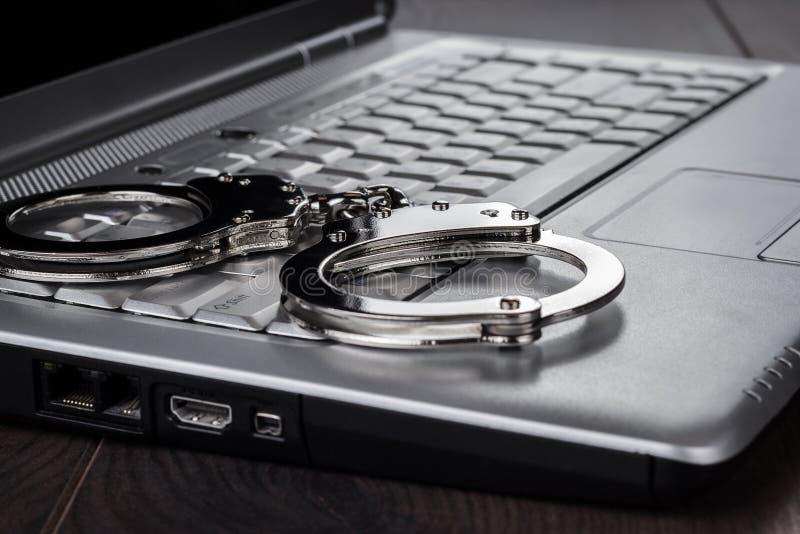 Algemas no conceito do crime do cyber do portátil fotografia de stock