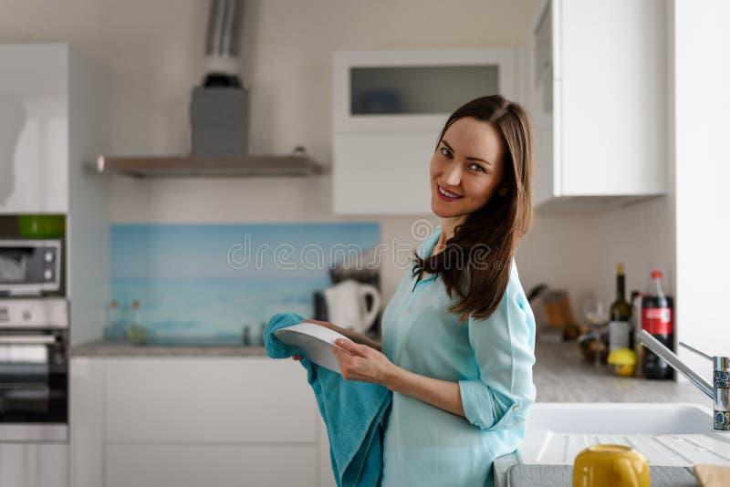 Algemeen portret van een jong meisje binnen een heldere keuken met een handdoek en een plaat in zijn handen Echt royalty-vrije stock fotografie