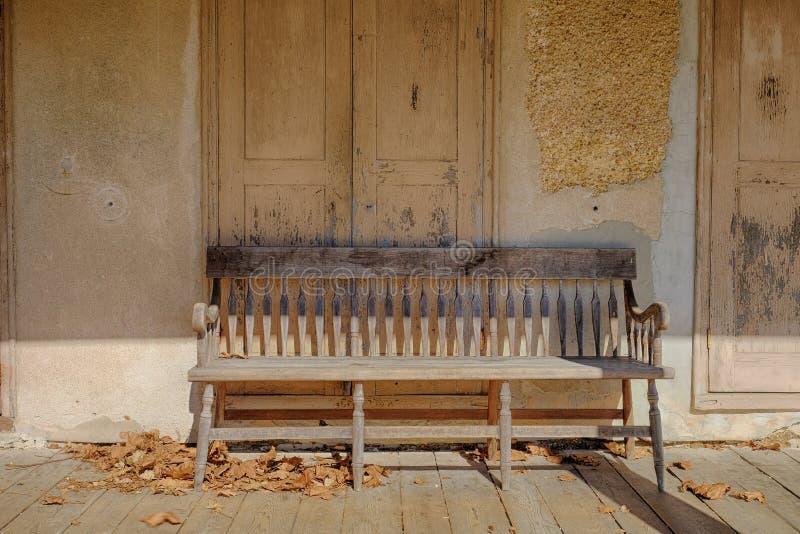 Algemene opslagmuur met een oude doorstane houten bank stock foto