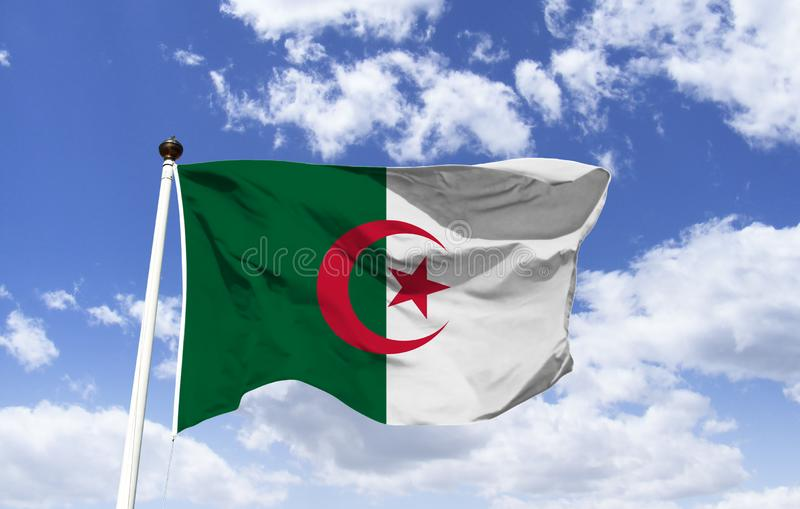 Algeria`s flag, fluttering under a blue sky. stock image
