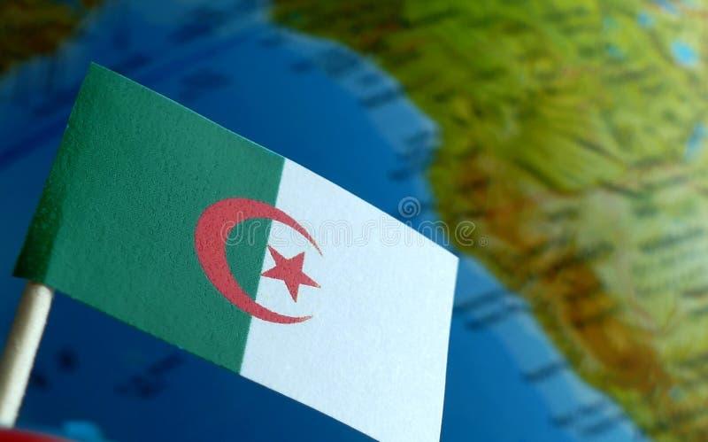 Algierczyk flaga z kuli ziemskiej mapą jako tło fotografia stock