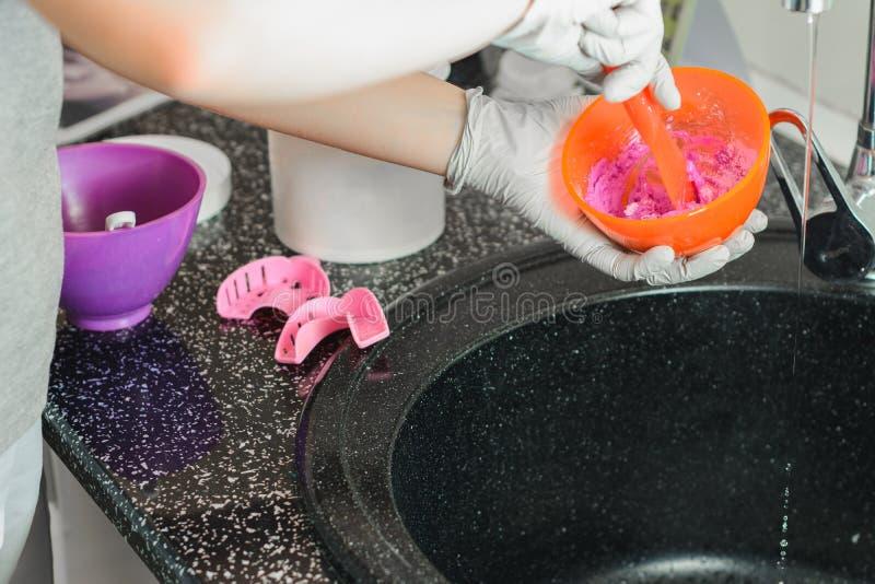 Alginata impressione, l'ortodontista prepara una miscela rosa per misurare la bocca del paziente immagini stock libere da diritti