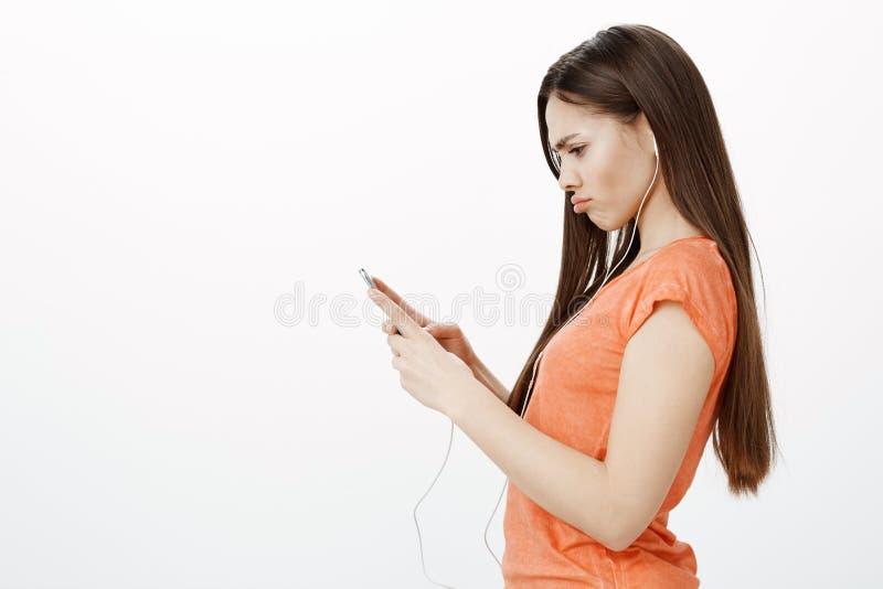 Algo correcto Hembra urbana elegante descontentada melancólica en la camiseta anaranjada, colocándose en perfil sobre gris fotos de archivo