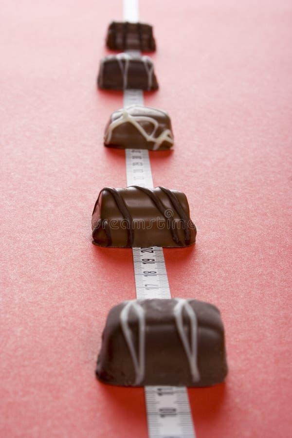 Algo de chocolates y de la medida fotografía de archivo