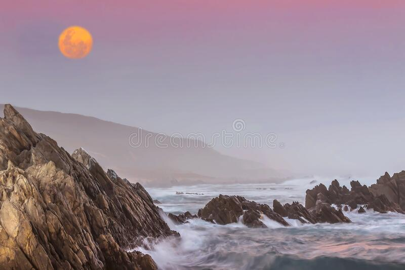 A pink full moon sunset on the wild rocky Indian Ocean coastline of Port Elizabeth, South Africa. Algoa Bay`s 40 km of breathtaking Indian Ocean coastline boasts stock photography